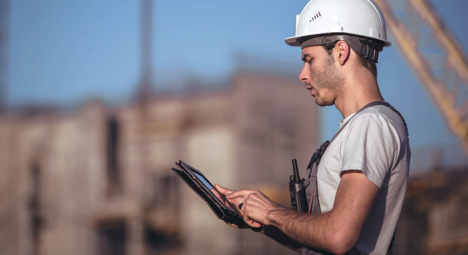 Construction worker works on a tablet